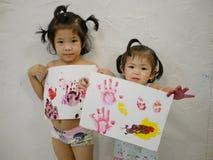 Dwa małej Azjatyckiej dziewczynki, siostry, cieszyli się pokazywać ich grafika po robić one samodzielnie - dzieci handprints zdjęcie stock