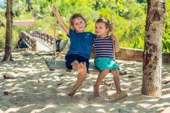 Dwa małej blondynki chłopiec ma zabawę na huśtawce na tropikalnym s zdjęcia royalty free