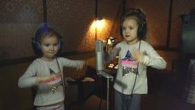 Dwa małej dziewczynki śpiewa w mikrofonie w hełmofonach zbiory