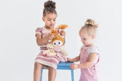 Dwa małej dziewczynki bawić się na białym tle fotografia royalty free