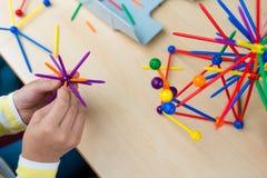 Dwa małej dziewczynki bawić się z udziałami kolorowy plastikowy kija ki Fotografia Stock