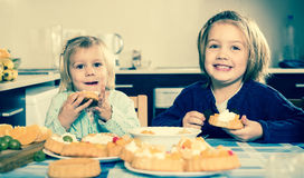 Dwa małej dziewczynki cieszy się ciasto z śmietanką obraz royalty free