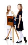 Dwa małej dziewczynki patrzeje rocznik kamerę Fotografia Stock
