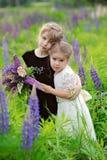 Dwa małej dziewczynki przy zielenieją pole w zmierzchu czasie z bukietem, Obraz Royalty Free