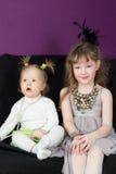 Dwa małej dziewczynki siedzi na czarnej kanapie fotografia royalty free
