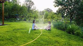 Dwa małej dziewczynki siedzi na zielonym gazonie blisko pracować ogrodowego kropidło zdjęcie wideo