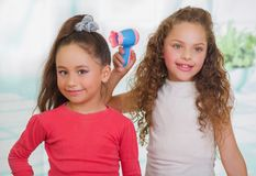Dwa małej pięknej dziewczyny pozuje dla kamery, kędzierzawa dziewczyna trzymają włosianą suszarkę i brunetka jest ubranym czerwon Zdjęcie Stock