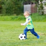 Dwa małej rodzeństwo chłopiec bawić się piłkę nożną i futbol na polu Obraz Royalty Free