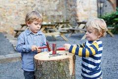 Dwa małej rodzeństwo chłopiec bawić się z młotem outdoors. Zdjęcia Royalty Free