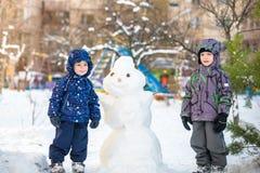 Dwa małej rodzeństwo dzieciaków chłopiec robi bałwanu, bawić się zabawę z śniegiem i ma na zimnym dniu, outdoors Aktywni czasów w Obrazy Royalty Free