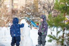 Dwa małej rodzeństwo dzieciaków chłopiec robi bałwanu, bawić się zabawę z śniegiem i ma na zimnym dniu, outdoors Aktywni czasów w Zdjęcia Royalty Free