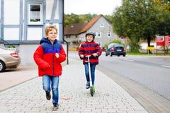 Dwa małej schoolkids chłopiec biega i jedzie na hulajnoga na jesień dniu Szczęśliwi dzieci w kolorowych ubraniach i miasto obraz stock