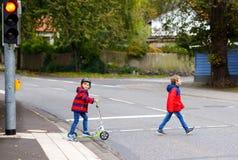 Dwa małej schoolkids chłopiec biega i jedzie na hulajnoga na jesień dniu Szczęśliwi dzieci w kolorowych ubraniach i miasto obrazy royalty free