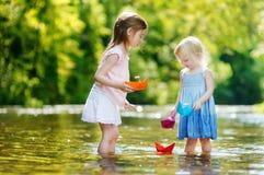 Dwa małej siostry bawić się z papierowymi łodziami obraz stock