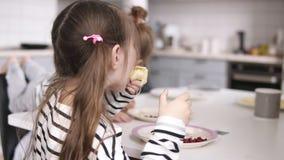 Dwa małej siostry jedzą bliny przy stołem z ojcem za one Boczny widok zbiory wideo