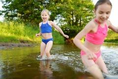 Dwa małej siostry ma zabawę na piaskowatej jezioro plaży na ciepłym i pogodnym letnim dniu Dzieciaki bawić się rzeką zdjęcia stock