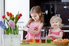 Dwa małej siostry maluje Wielkanocnych jajka Obrazy Royalty Free