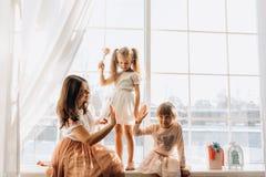 Dwa małej siostry ubierali w pięknych sukniach i tam siedzi na windowsill obok lustra potomstwo matka obraz stock