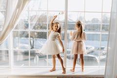 Dwa małej siostry ubierali w pięknym suknia stojaku na windowsill obok lustra zdjęcie royalty free