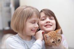 Dwa małej siostry z kotem fotografia stock