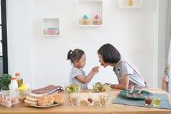 Dwa małych dziewczynek łasowania kucharzi w kuchni i sałatka zdjęcia stock