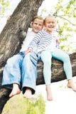 Dwa małych dziewczynek obsiadanie na falowaniu i drzewie jej naga opłata Fotografia Stock