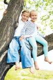 Dwa małych dziewczynek obsiadanie na falowaniu i drzewie jej naga opłata Zdjęcia Royalty Free