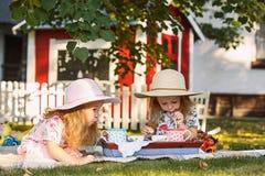 Dwa małej dziewczynki siedzi na zielonej trawie Zdjęcie Royalty Free
