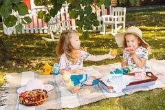 Dwa małej dziewczynki siedzi na zielonej trawie Obraz Stock