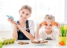 Dwa małej siostry trzyma colourful Wielkanocnych jajka Zdjęcie Royalty Free