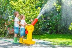 Dwa małego dziecka bawić się z ogrodowym wężem elastycznym i wodą w lecie Zdjęcie Stock
