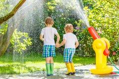 Dwa małego dziecka bawić się z ogrodowym wężem elastycznym w lecie Fotografia Royalty Free