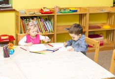 Dwa małego dziecka rysuje z kolorowymi ołówkami w preschool przy stołem dziewczyny i chłopiec rysunek w dziecinu Fotografia Stock