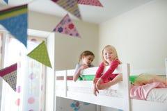 Dwa małej siostry błaź się wokoło, bawić się i ma zabawę w bliźniaczym koi łóżku, Zdjęcie Stock