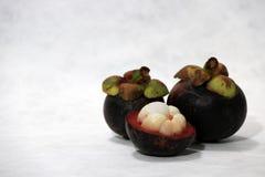 Dwa mangostanu i jeden łupa na białym tle fotografia stock