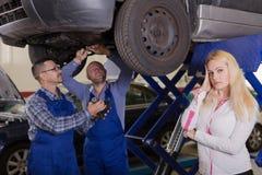 Dwa mechanika próbuje oszukiwać klienta przy warsztatem fotografia stock