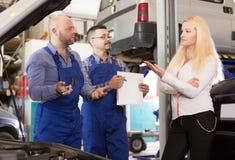 Dwa mechanika próbuje oszukiwać klienta przy warsztatem Fotografia Royalty Free