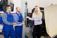 Dwa mechanika próbuje oszukiwać klienta przy warsztatem Obraz Stock