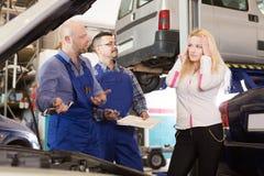 Dwa mechanika próbuje oszukiwać klienta przy warsztatem Obrazy Stock