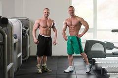 Dwa Mięśniowego mężczyzna Napina mięśnie W Gym Obrazy Royalty Free