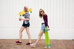 Dwa miastowej dziewczyny jest ubranym w kratkę koszula iść wzdłuż ulicy w mieście z longboards obraz stock