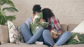 Dwa mieszającego biegowego kędzierzawego dziewczyna przyjaciela siedzi na leżanki i zegarka prawdziwym strasznym filmu na TV i je zbiory wideo