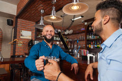 Dwa mieszanek Biegowy mężczyzna Wznosi toast W Prętowych Clink szkłach, Pije Piwnych chwytów kubki, Rozochocony przyjaciół Spotyk Obraz Stock