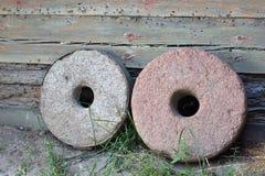 Dwa millstones na starym drewnianym ?ciennym tle zdjęcia royalty free