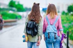 Dwa modniś dziewczyny z deskorolka outdoors w zmierzchu świetle Aktywne sporty kobiety ma zabawę w łyżwa parku wpólnie Zdjęcie Stock