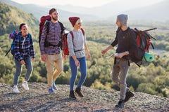 Dwa modniś pary wycieczkuje w górach podczas długiej wycieczki z plecakami Szczęśliwa caucasian grupa podróżnicy obraz stock