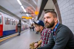 Dwa modnisia mężczyzna siedzi przy podziemnym estradowym czekaniem Obraz Royalty Free