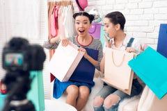 Dwa mody blogger dziewczyn spojrzenie zdumiewał przy kolorowymi torbami kamera fotografia stock