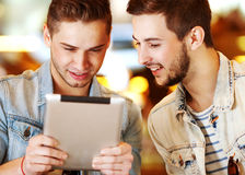 Dwa młodzi człowiecy, ucznia używa pastylka komputer w kawiarni/ Fotografia Royalty Free