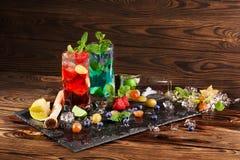 Dwa mojitos na drewnianym tle Koktajle z jagodami, mennicą i lodem, Alkoholiczny błękitny mojito Wyśmienicie czerwony mojito kosm zdjęcie stock